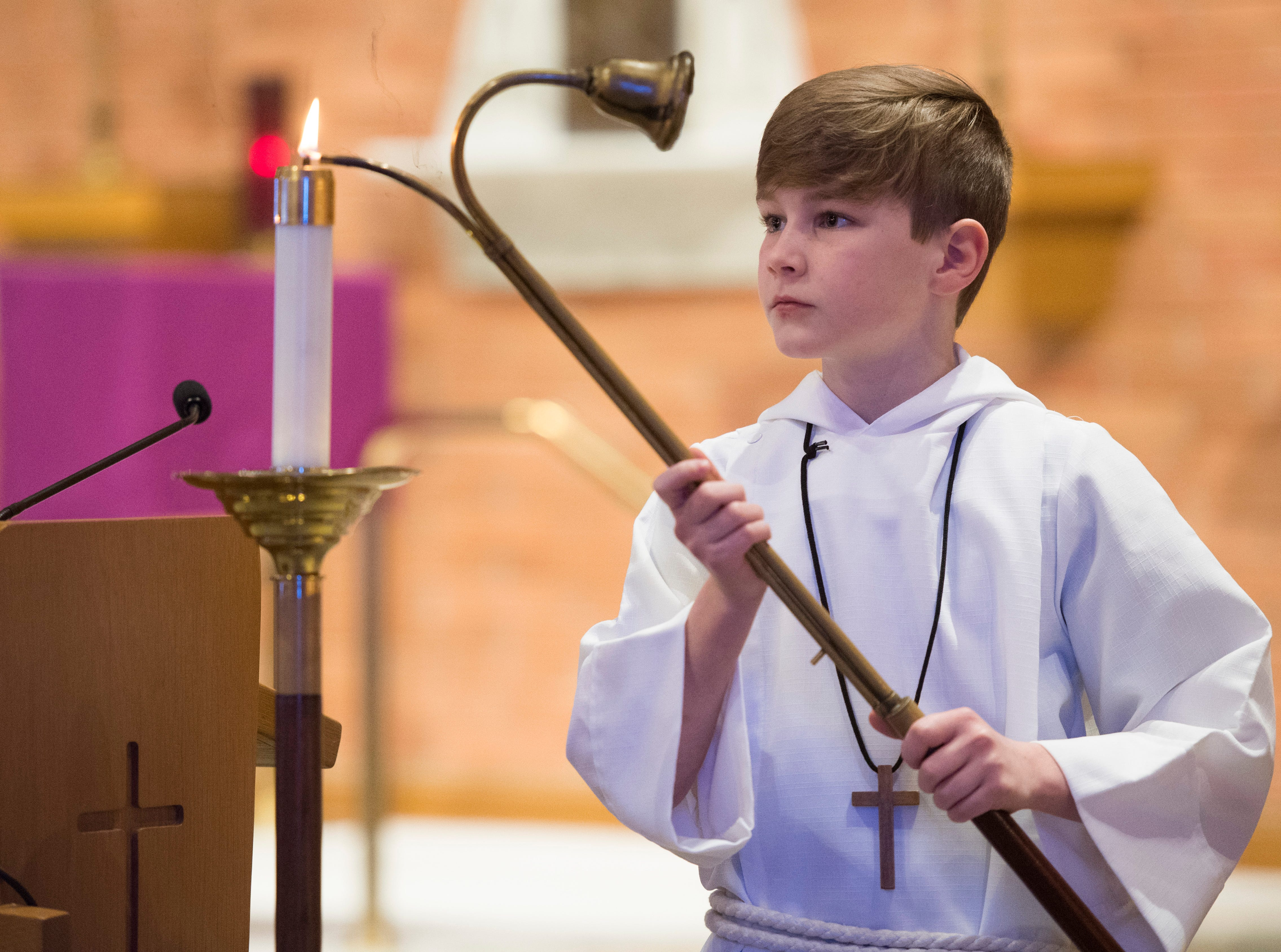 Corpus Christi sixth-grader Caden Willis lights a candle at the alter before the Ash Wednesday Mass Wednesday, March 6, 2019.