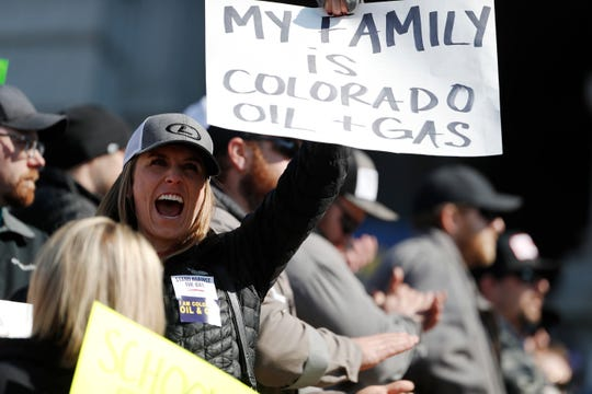 Audrey Carlson of Denver waves a placard during a rally outside the State Capitol Tuesday, March 5, 2019 in opposition of lawmakers' plan to advance a bill to overhaul the state's oil and gas regulations. (AP Photo/David Zalubowski)