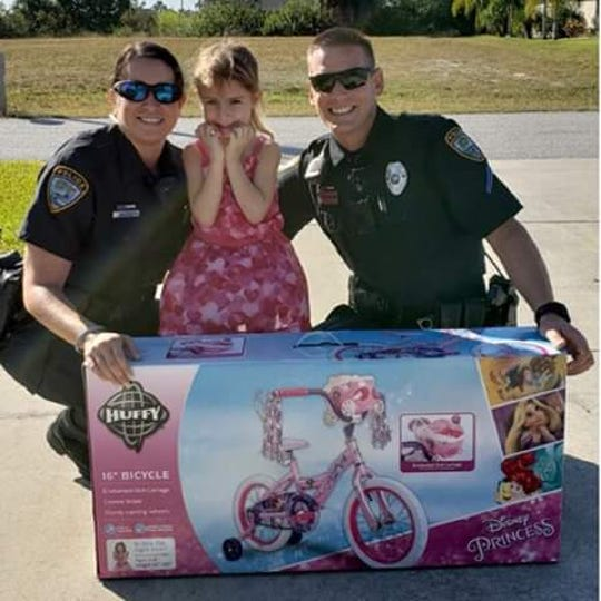 Two Cape Coral police officers present a 4-year-old girl with a new bike. The girl's mother had purchased a bike for her daughter's birthday, but it was damaged in a car accident.