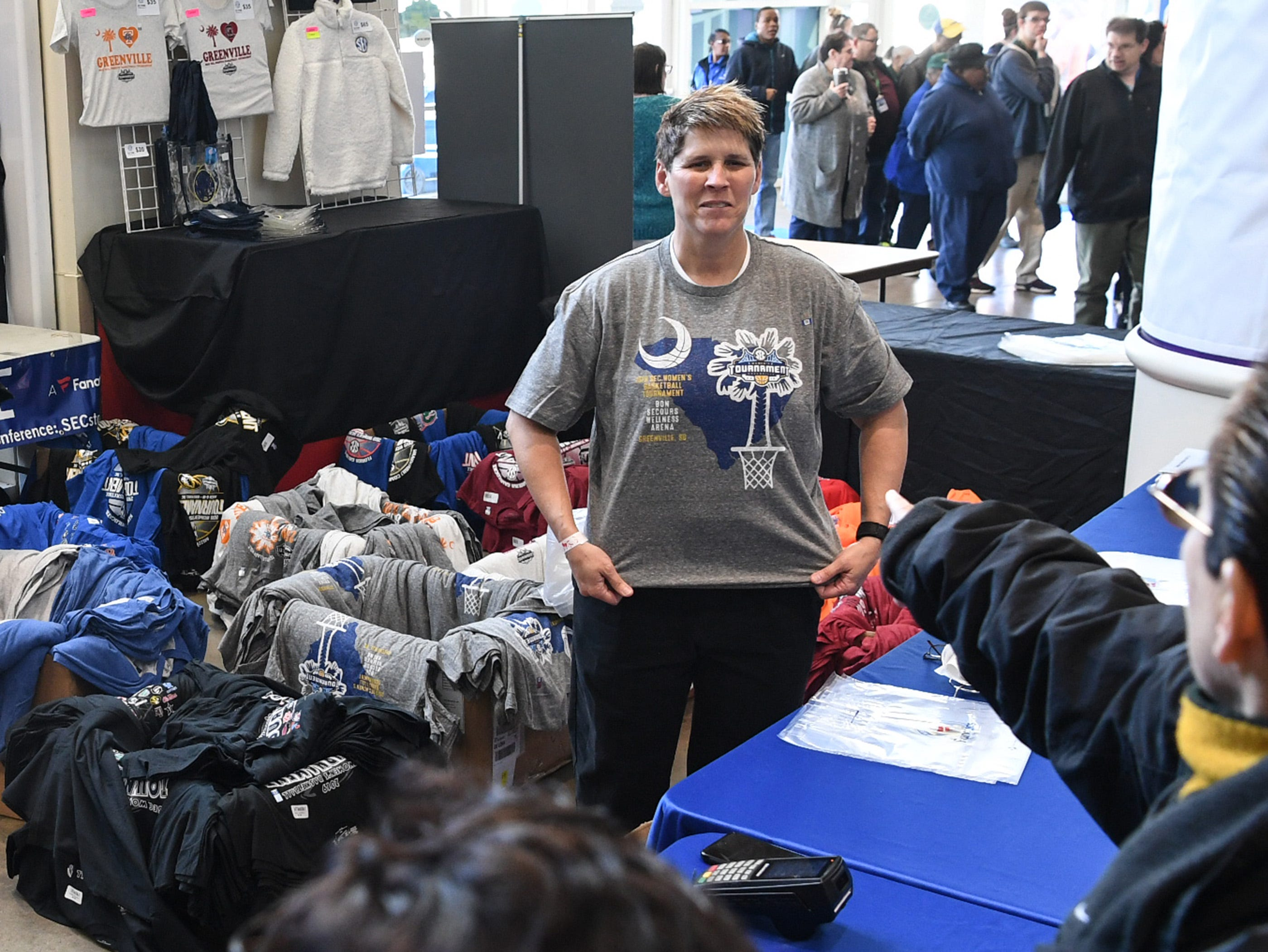 Kelly Lack of Woodruff shows off a SEC t-shirt for sale to fans before the first SEC Women's basketball tournament game, Ole Miss and Florida, in Greenville Wednesday. The tournament lasts through Sunday.