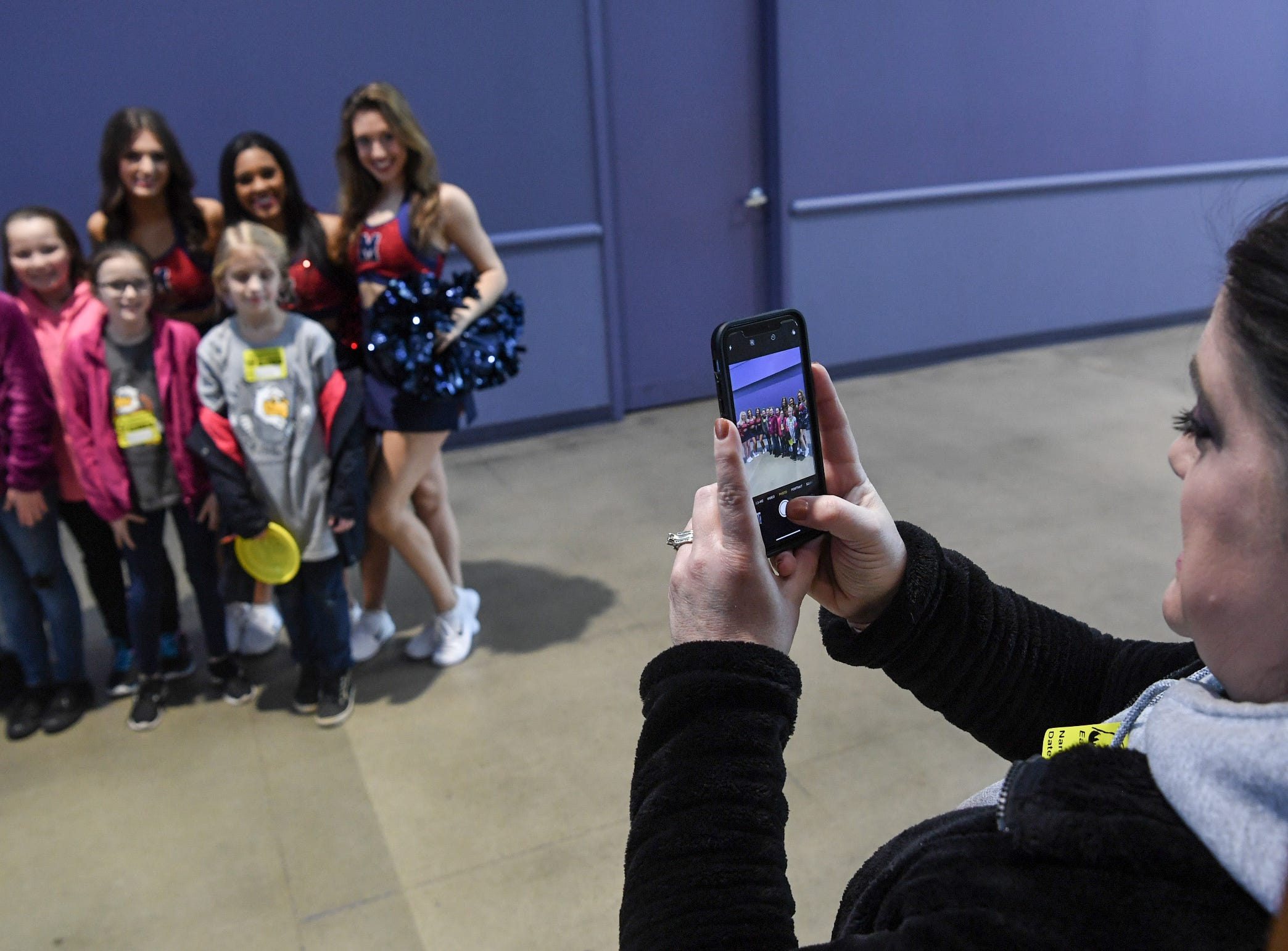Amy Cash takes photos of her children from Chesnee Elementary before the first SEC Women's basketball tournament game, Ole Miss and Florida, in Greenville Wednesday. The tournament lasts through Sunday.