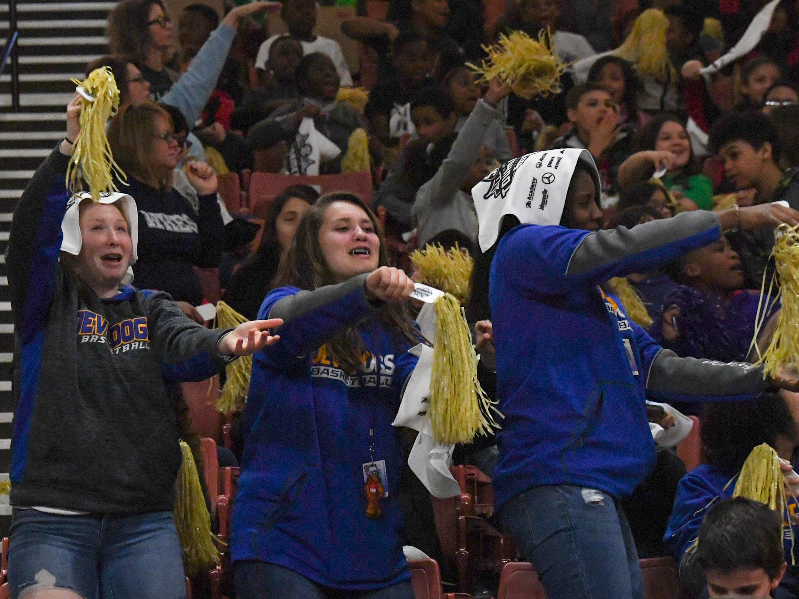 """Summer Baties, left, Emma Baker, and Kloey Pickens, basketball players from Travelers Rest High School, make arm motions of a shark bite as popular song """"Baby Shark""""  is played during a break at the first SEC Women's basketball tournament game with Ole Miss and Florida in Greenville Wednesday. The tournament lasts through Sunday."""