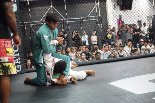 Adrian Anulao sets up an arm bar on Mark Pachkoski during Steel Athletics' Glorified Sparring event on March 1st, held to raise money for the Tamuning Skatepark.