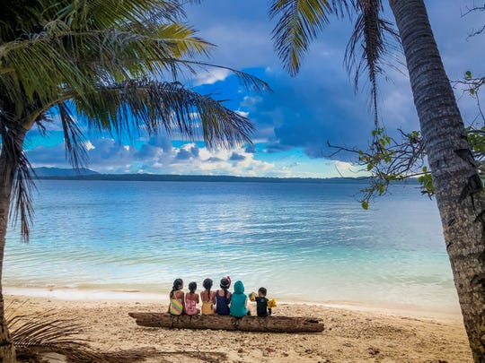 Photo of children sitting on a log at Family Beach in Piti.