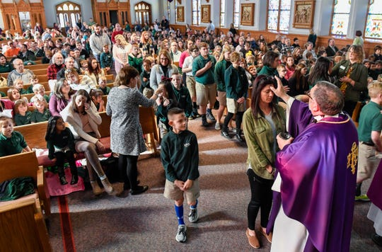 Father Larry McBride conducts the morning, all-school Ash Wednesday Mass at Henderson's Holy Name of Jesus Catholic Church Wednesday for students, staff and families from Holy Name School.