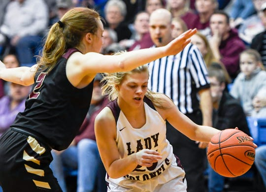 Henderson County's Kaytlan Kemp (20) drives against defense from Webster County's Marissa Austin (2) as the Webster County Lady Trojans play the Henderson County Colonels for the Girls Second Region Championship at the Rocket Arena in Marion Tuesday, March 5, 2019.