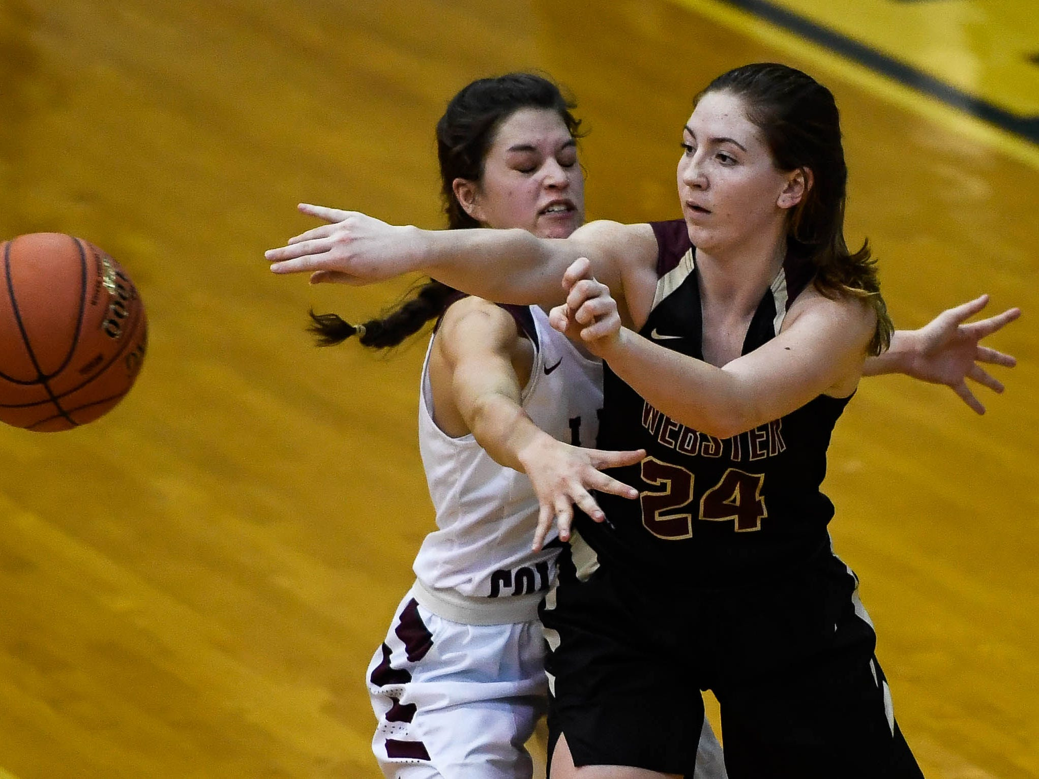 Webster County's Adeline McDyer (24) passes under defensive pressure from Henderson County's Katie Rideout (10) as the Webster County Lady Trojans play the Henderson County Colonels for the Girls Second Region Championship at the Rocket Arena in Marion Tuesday, March 5, 2019.