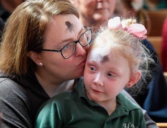 Sarah Hopper gives her daughter Kenli, 5, a peck on the cheek during the morning. all-school Ash Wednesday Mass at Henderson's Holy Name of Jesus Catholic Church.