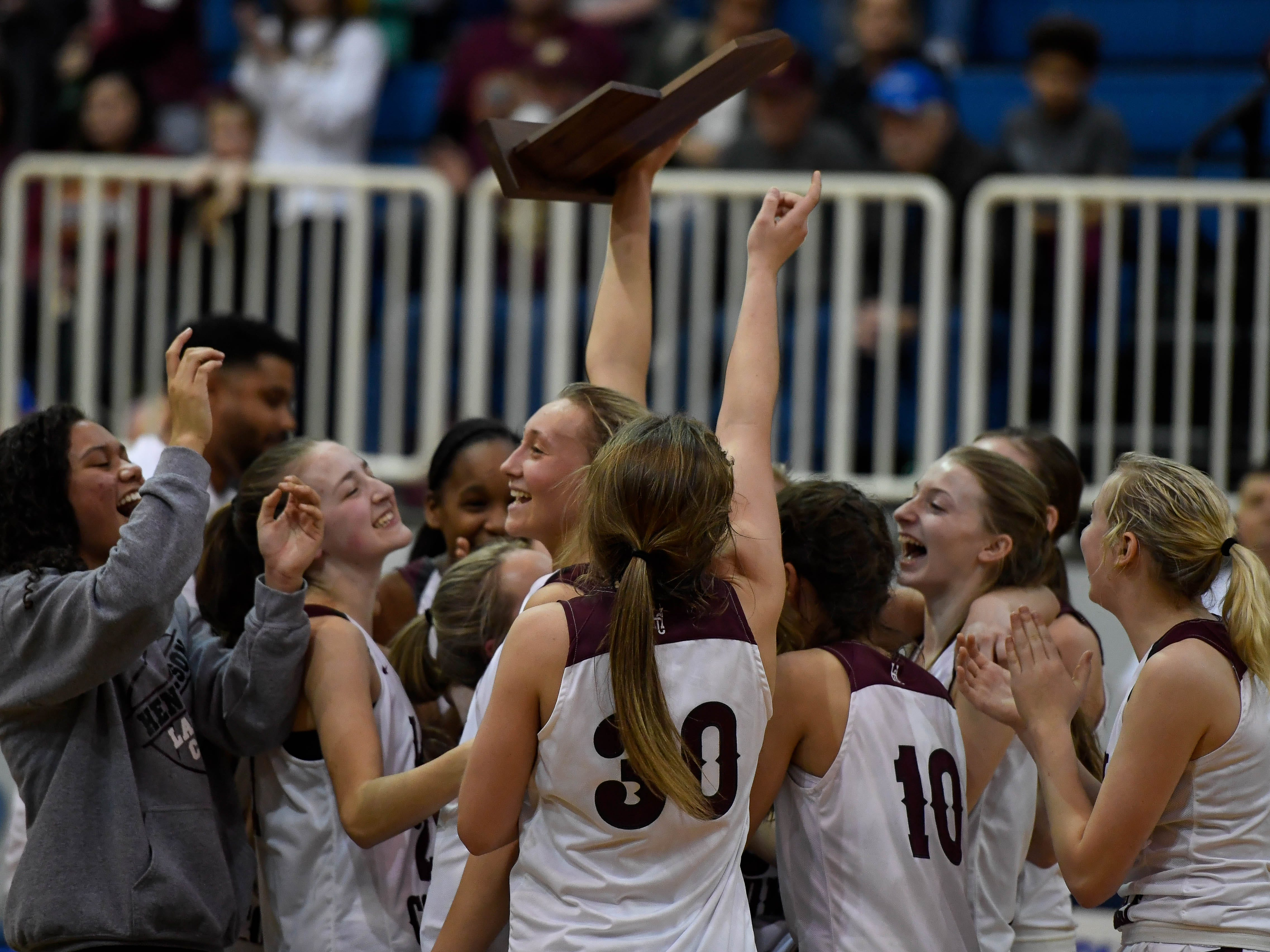 The Henderson County Colonels celebrate with the Girls Second Region Championship trophy after defeating the Webster County Lady Trojans at the Rocket Arena in Marion Tuesday, March 5, 2019.