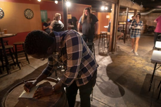 Matt Waweru, a recent Purdue graduate, signs up for a weekly open microphone run by Rocketship Comedy at Shoefly Public House, Indianapolis, Monday, Sept. 17, 2018.