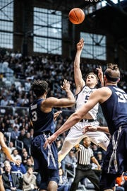 Butler University's Paul Jorgensen (5) shoots over Xavier's Quentin Goodin (3), and Zach Hankins (35), during a game between the Butler University Bulldogs and Xavier University Musketeers at Hinkle Fieldhouse on Tuesday, March 5, 2019.