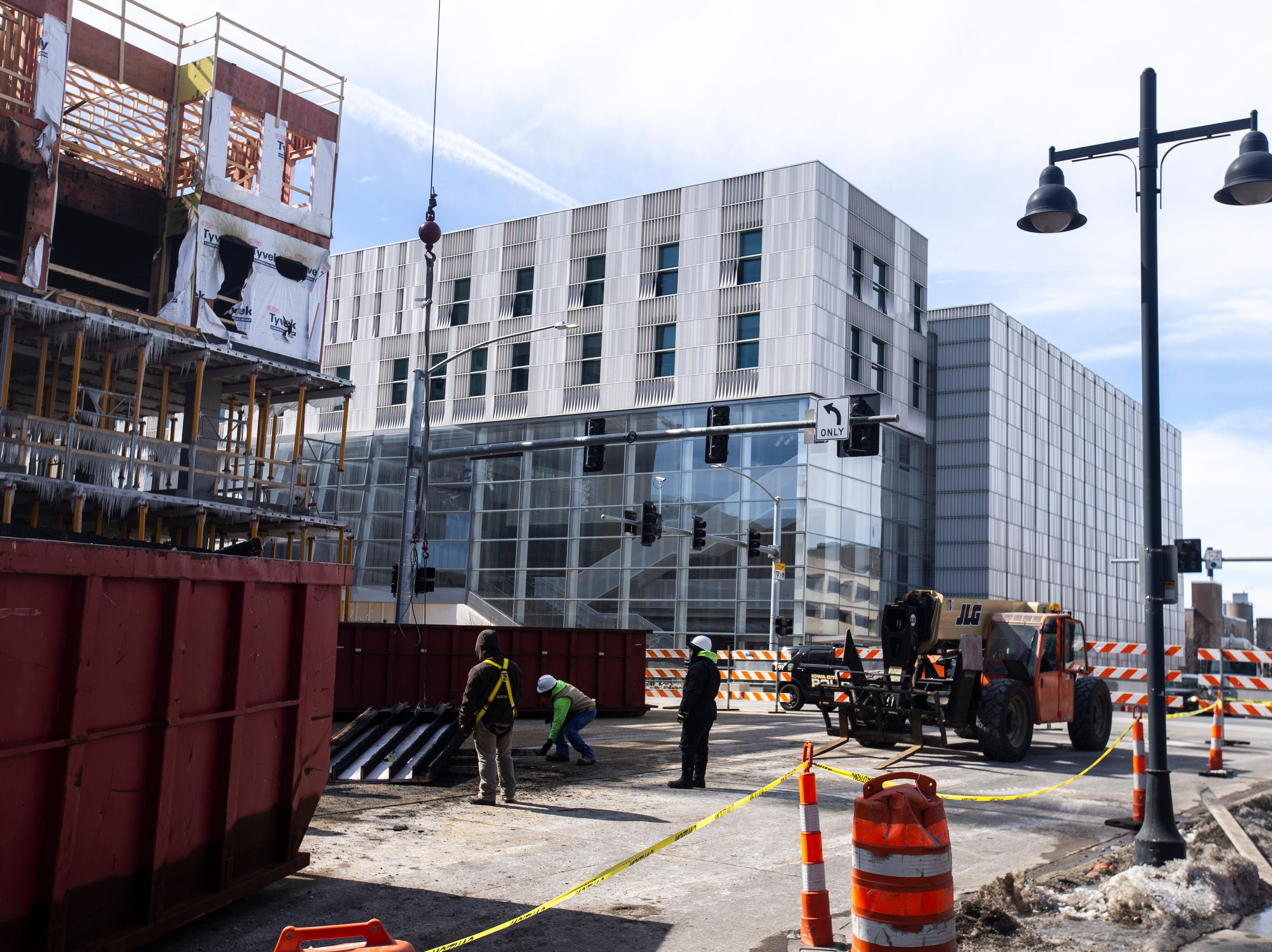 Workers begin to take down fire damage at the Hieronymous Square construction site on Wednesday, March 6, 2019, at 314 S. Clinton Street in downtown Iowa City, Iowa.