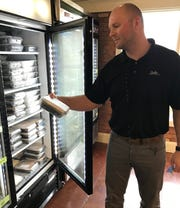 Bradford Foster of Madison County checks out entrees that are stocked in the freezers at Olivia's Food Emporium in Ridgeland.