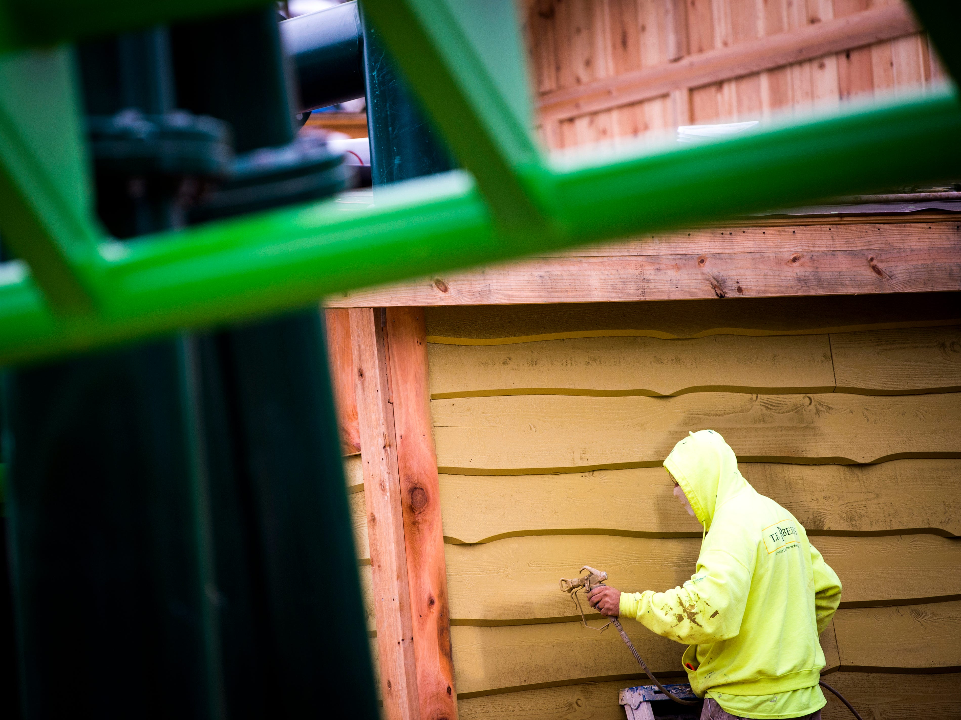 A construction worker adds paint to a building in Dollywood's new Wildwood Grove area of the park on Tuesday, February 19, 2019.