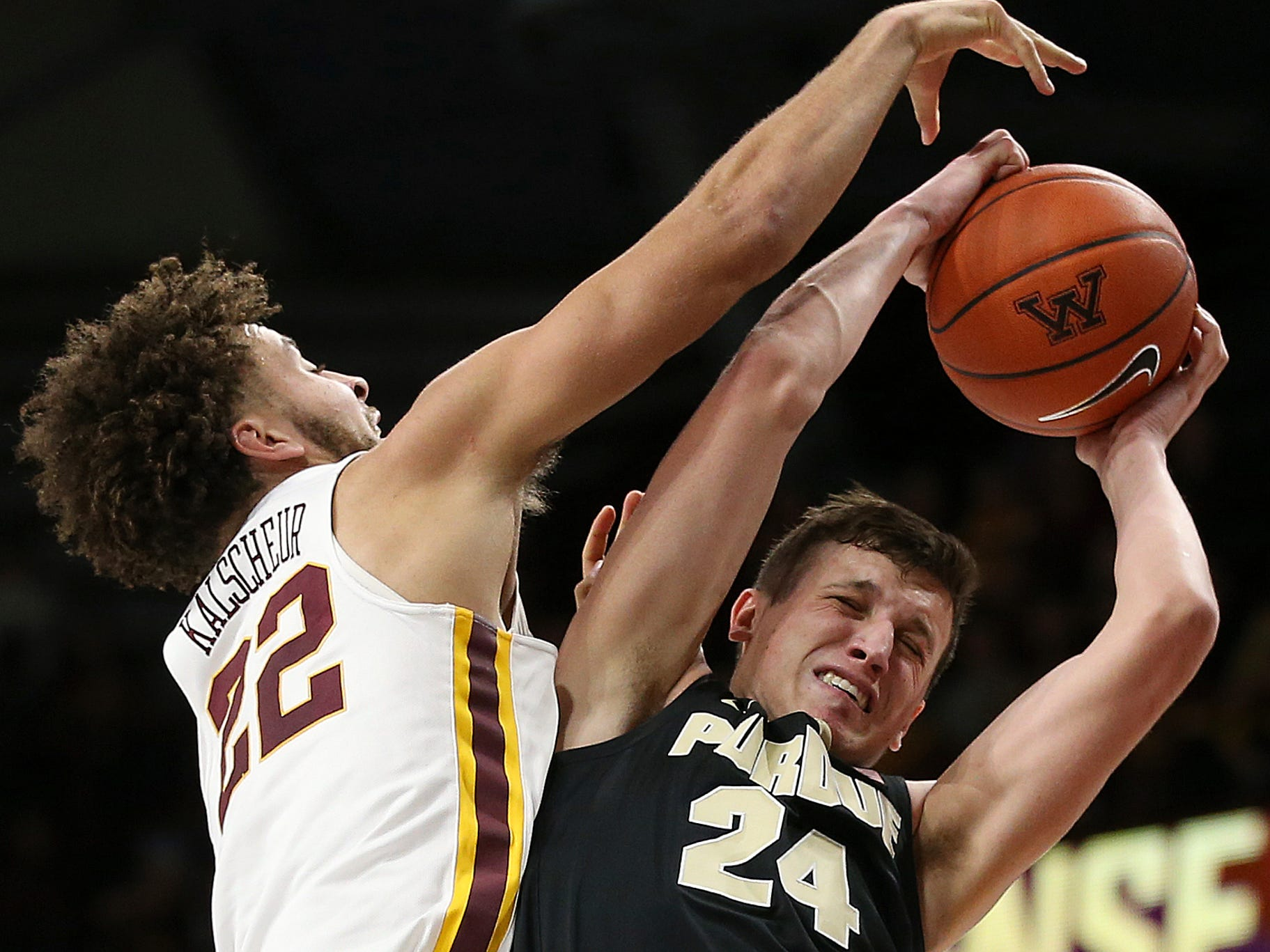 Purdue's Grady Eifert tries to hold onto the ball against Minnesota's guard Gabe Kalscheur during the second half of an NCAA basketball game Tuesday, March 5, 2019, in Minneapolis. Minnesota won 73-69.