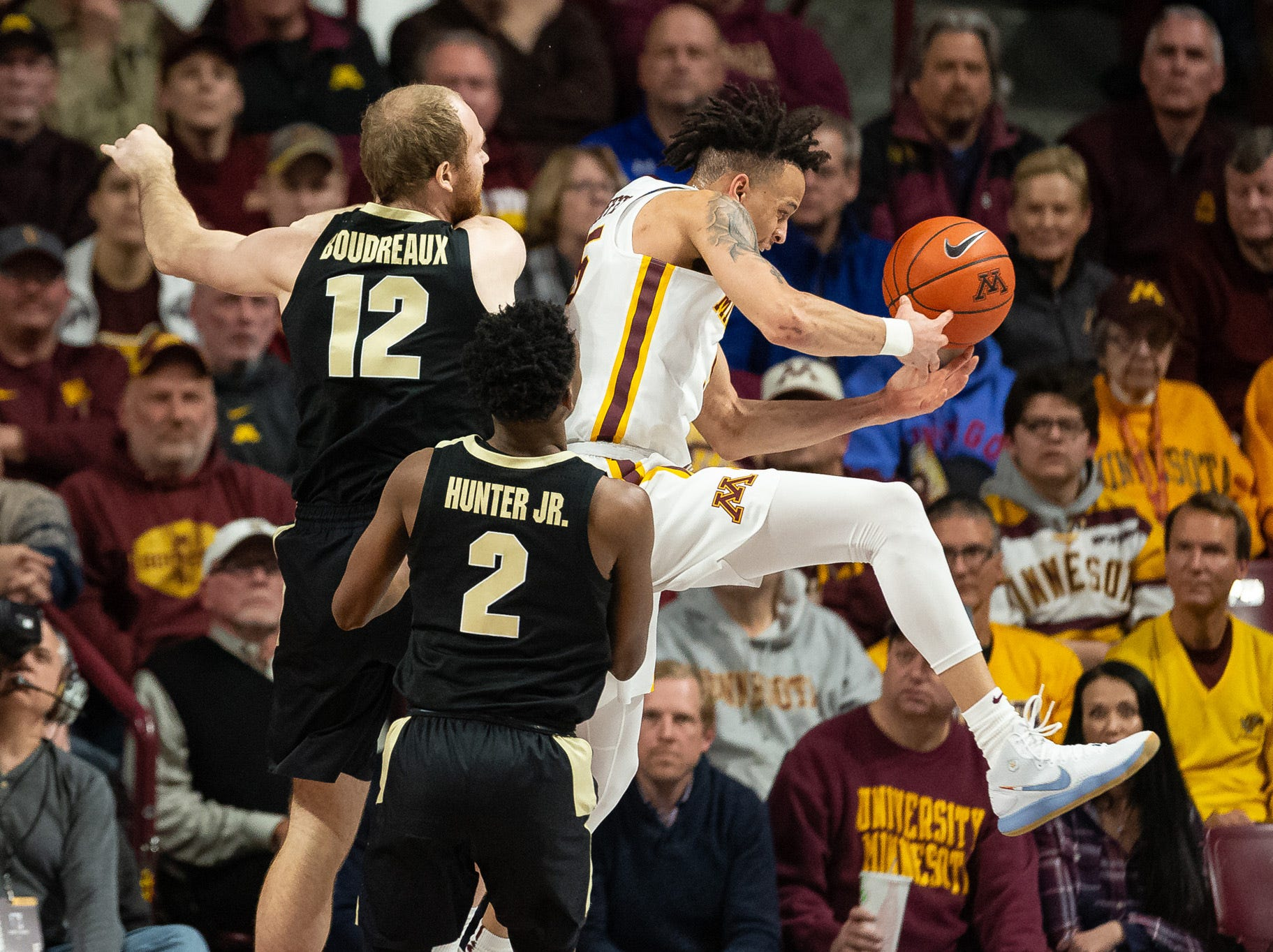 Mar 5, 2019; Minneapolis, MN, USA; Minnesota Gophers guard Amir Coffey (5) rebounds the ball as Purdue Boilermakers forward Evan Boudreaux (12) defends during the first half at Williams Arena. Mandatory Credit: Harrison Barden-USA TODAY Sports