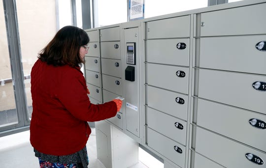 Fairfield County Library Director Becky Shaade scans her library card to open a locker at the self-serve library kiosk Wednesday, March 6, 2019, in Millersport. Patrons can request books not in the kiosk be delivered to the lockers for pickup.