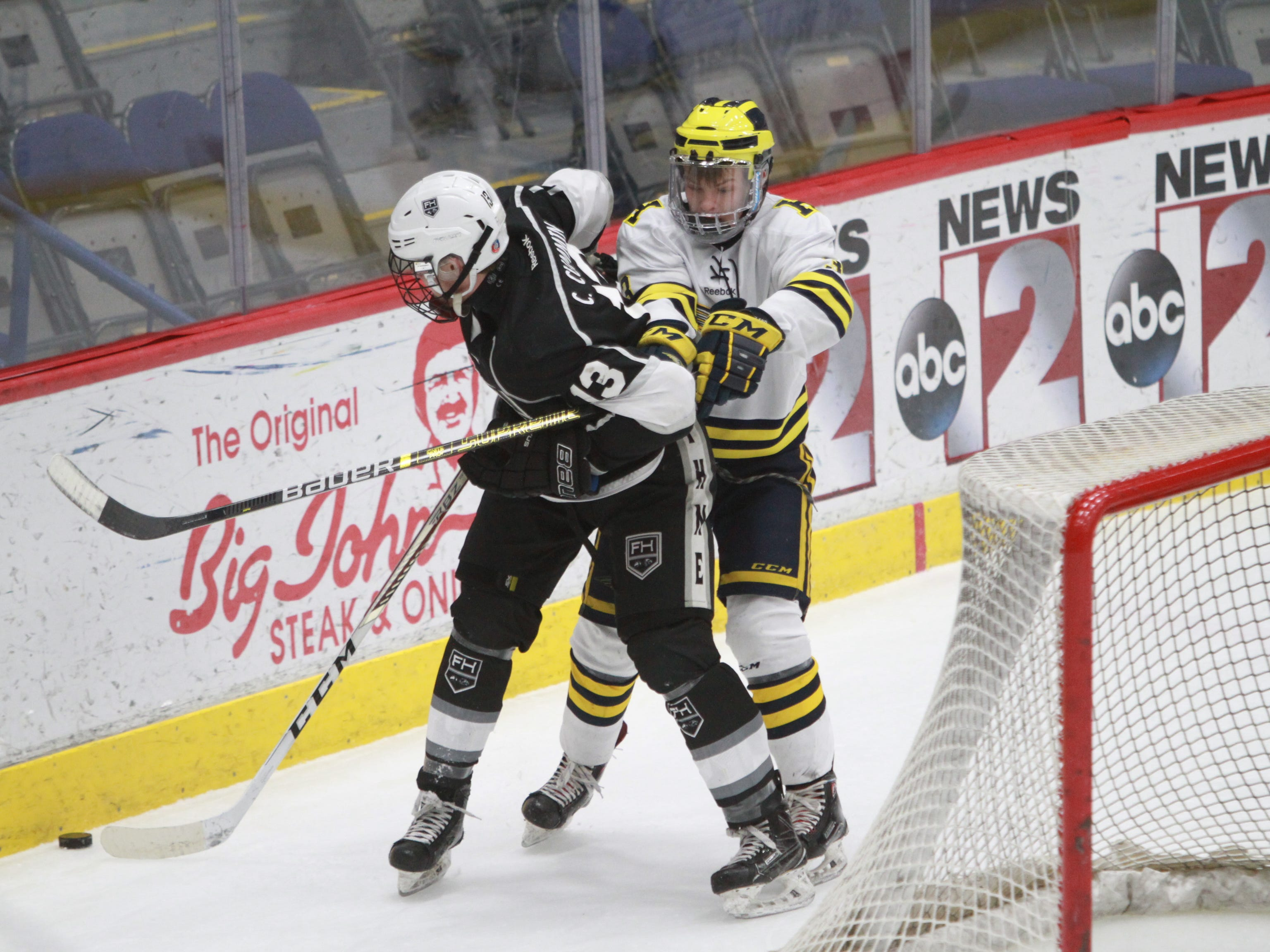 Hartland's Benny Tervo (right) battles for the puck behind the net with Forest Hills Eastern's Cure Cumming in a state hockey quarterfinal on Tuesday, March 5, 2019.