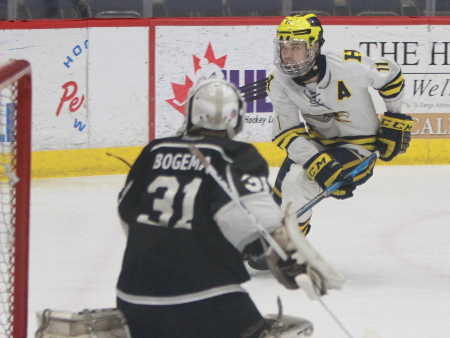 Hartland's Gabe Anderson follows up on his shot against Forest Hills Eastern goalie Brenden Bogema during the state Division 2 hockey quarterfinals in Flint on Tuesday, March 5, 2019.