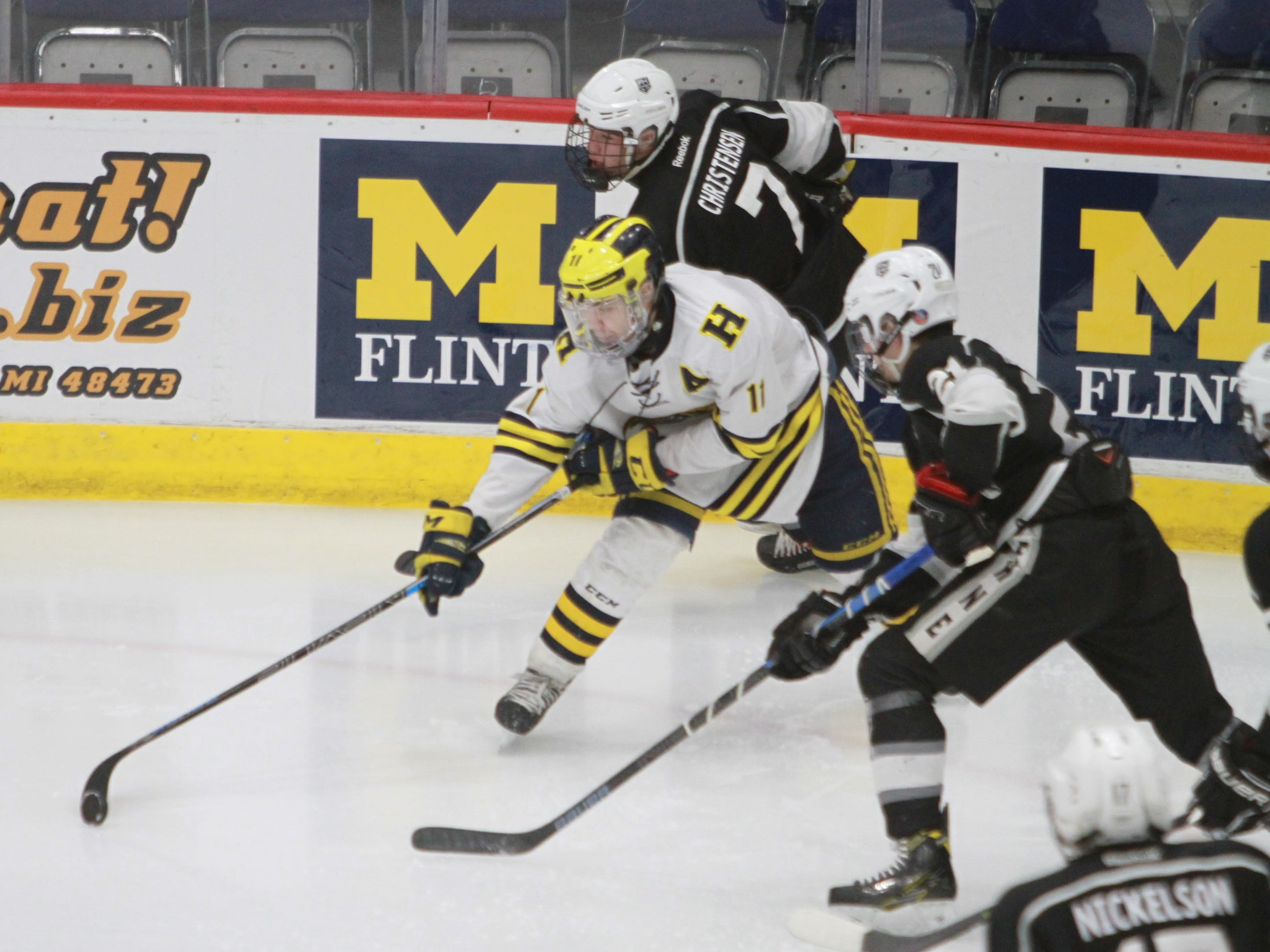 Hartland's Gabe Anderson (11) stickhandles while surrounded by Forest Hills Eastern's Ryan Almassian (21) and Noah Christensen (7) during the state Division 2 hockey quarterfinals in Flint on Tuesday, March 5, 2019.