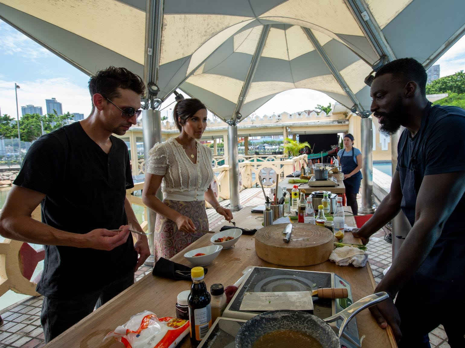 """Guest Judge Abe Conlon and host Padma Lakshmi talk to contestant Eric Adjepong about his dish on """"The Tao of Macau,"""" episode 14 of Bravo's 'Top Chef:' Kentucky season."""
