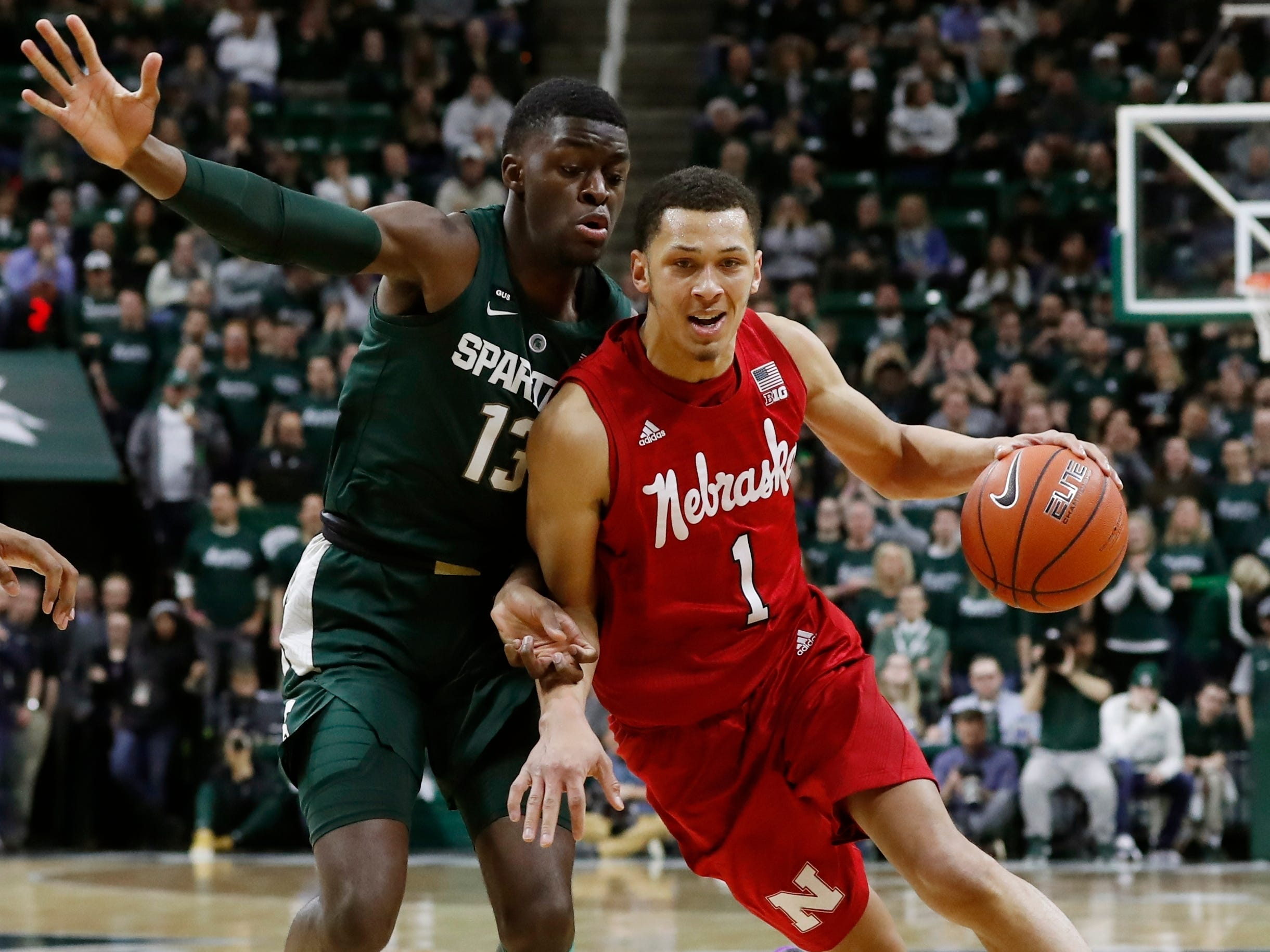 Nebraska guard Amir Harris drives against the defense of Gabe Brown, who played a big role for the Spartans Tuesday night.