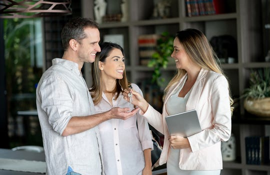 Real estate agent handing the keys to customers at their new home while she holds a tablet and everybody looking very happy and smiling