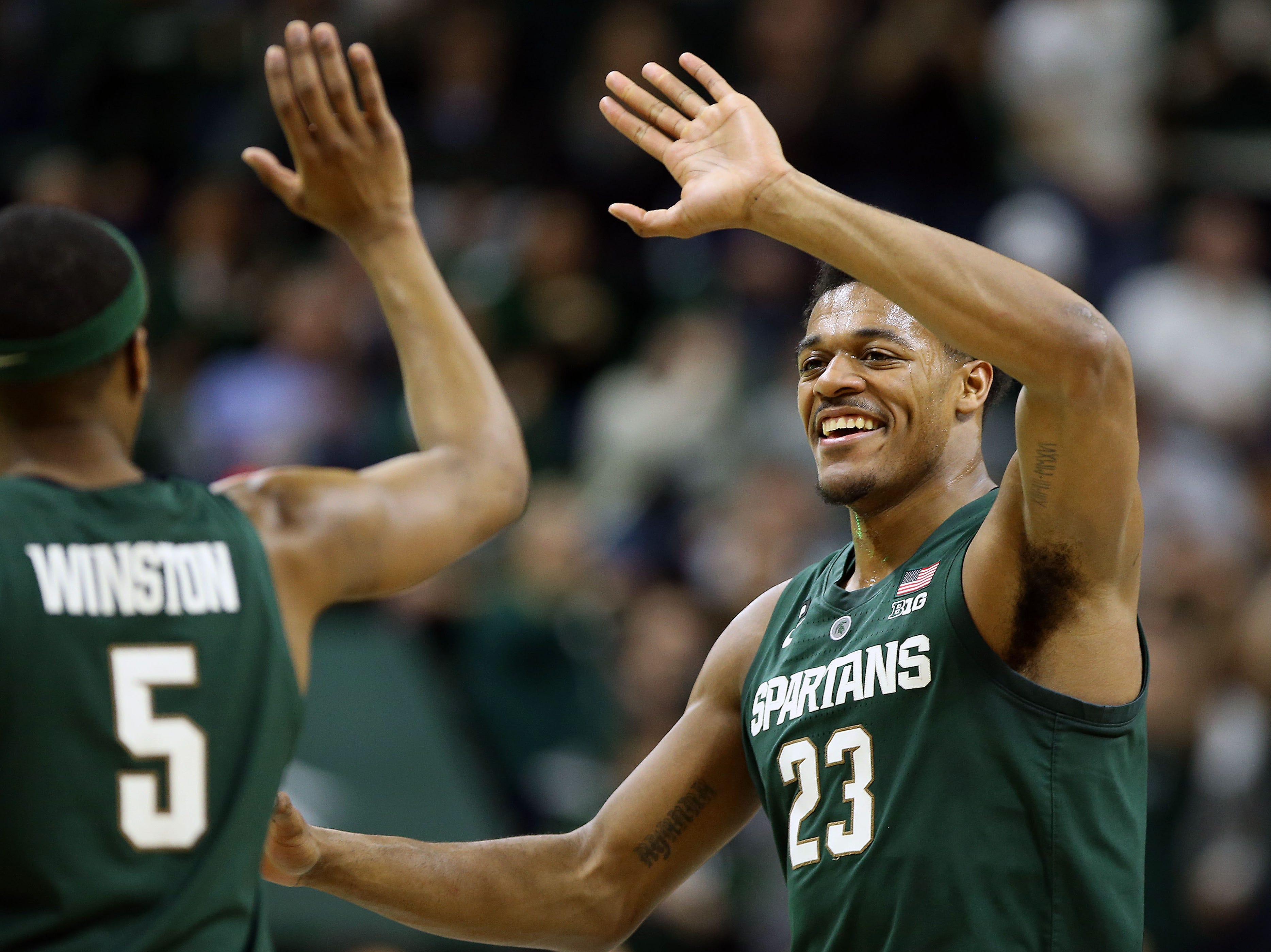 Mar 5, 2019; East Lansing, MI, USA; Michigan State Spartans forward Xavier Tillman (23) reacts with Michigan State Spartans guard Cassius Winston (5) during the first half of a game against the Nebraska Cornhuskers at the Breslin Center. Mandatory Credit: Mike Carter-USA TODAY Sports