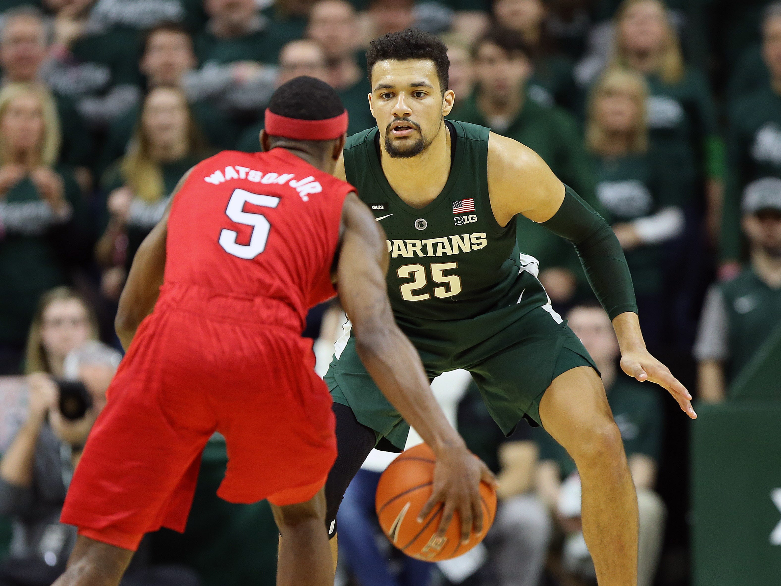 Mar 5, 2019; East Lansing, MI, USA; Michigan State Spartans forward Kenny Goins (25) looks on as Nebraska Cornhuskers guard Glynn Watson Jr. (5) brings the ball downcourt during the second half at the Breslin Center. Mandatory Credit: Mike Carter-USA TODAY Sports