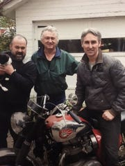 "Lexington musician and car collector Timothy Corwin, center, is shown with Frank Fritz and Mike Wolfe, holding Corwin's cat Bella, when the ""American Pickers"" came to Corwin's farm. The episode will air Monday."