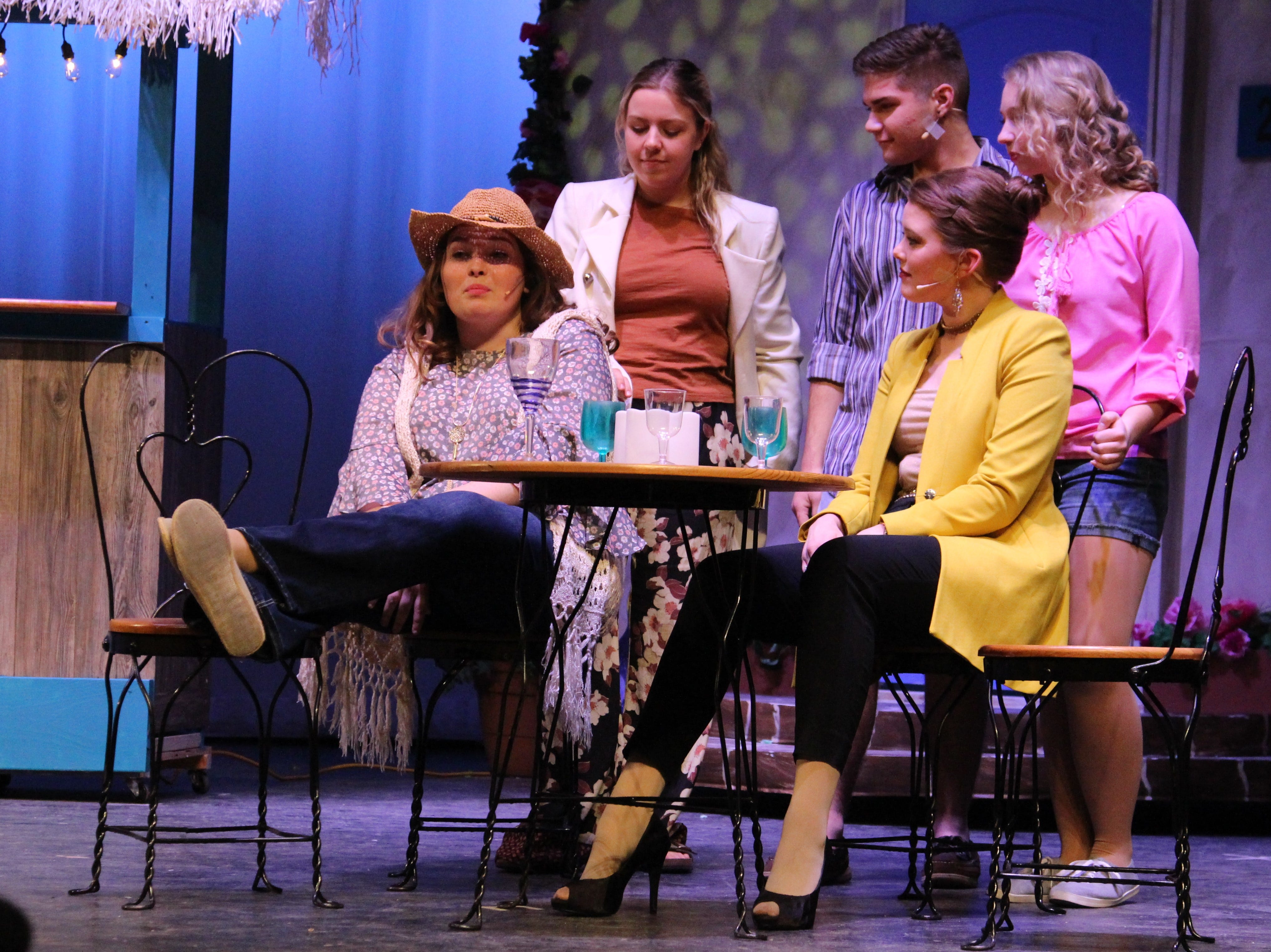 "Senior Shea Edler (left) —playing lead Donna Sheridan, whose daughter Sophie is about to get married— sits at ""her small Greek restaurant"" surrounded by guest and old friends during a rehearsal of River Valley High School's production of ""Mamma Mia."" The show will be held in the school's auditorium and it is $11 for general admission."