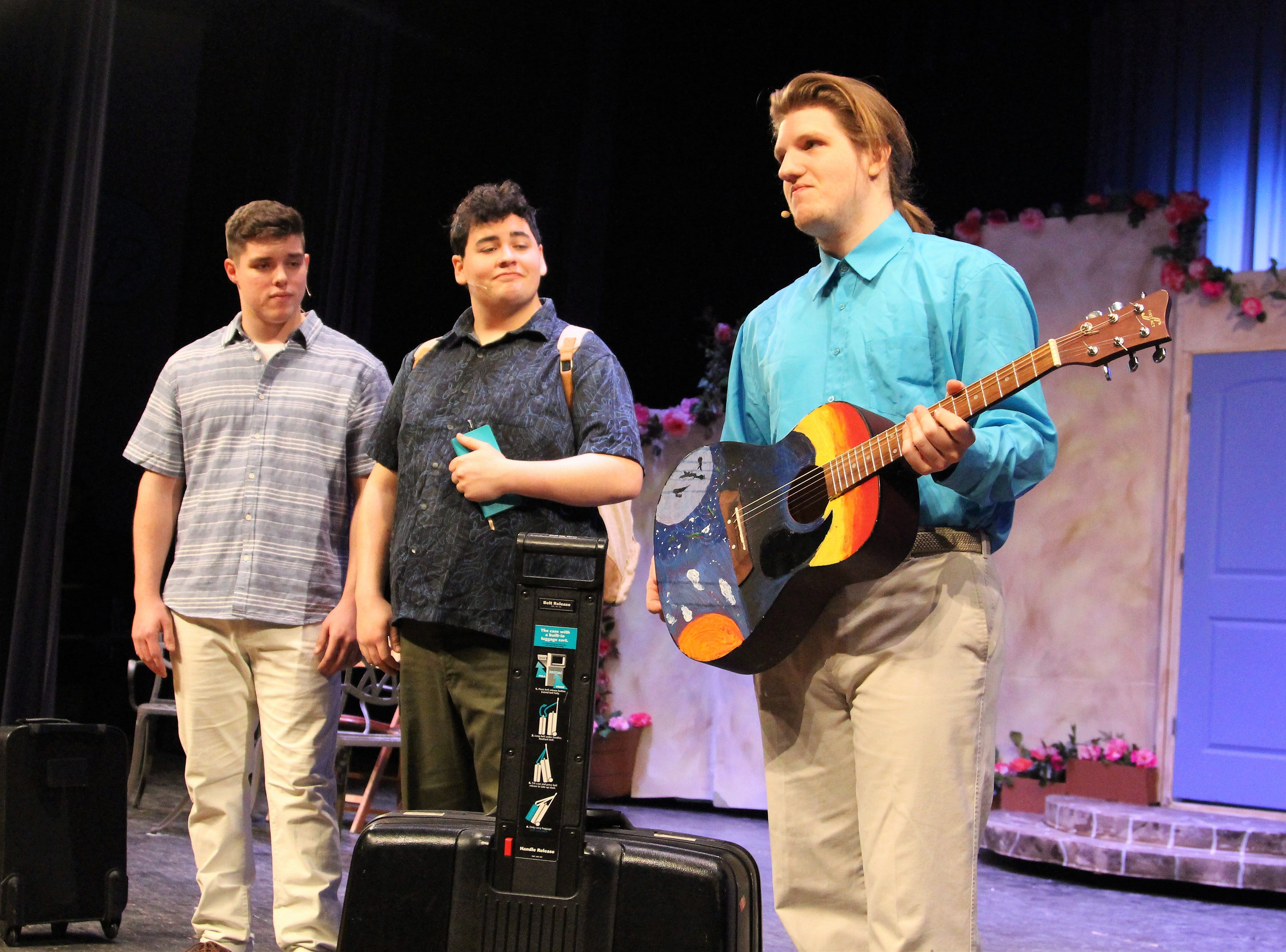"River Valley senior Ryan Anderson (right), playing British banker Harry Bright, picks up the guitar during an evening rehearsal of ""Mamma Mia."""
