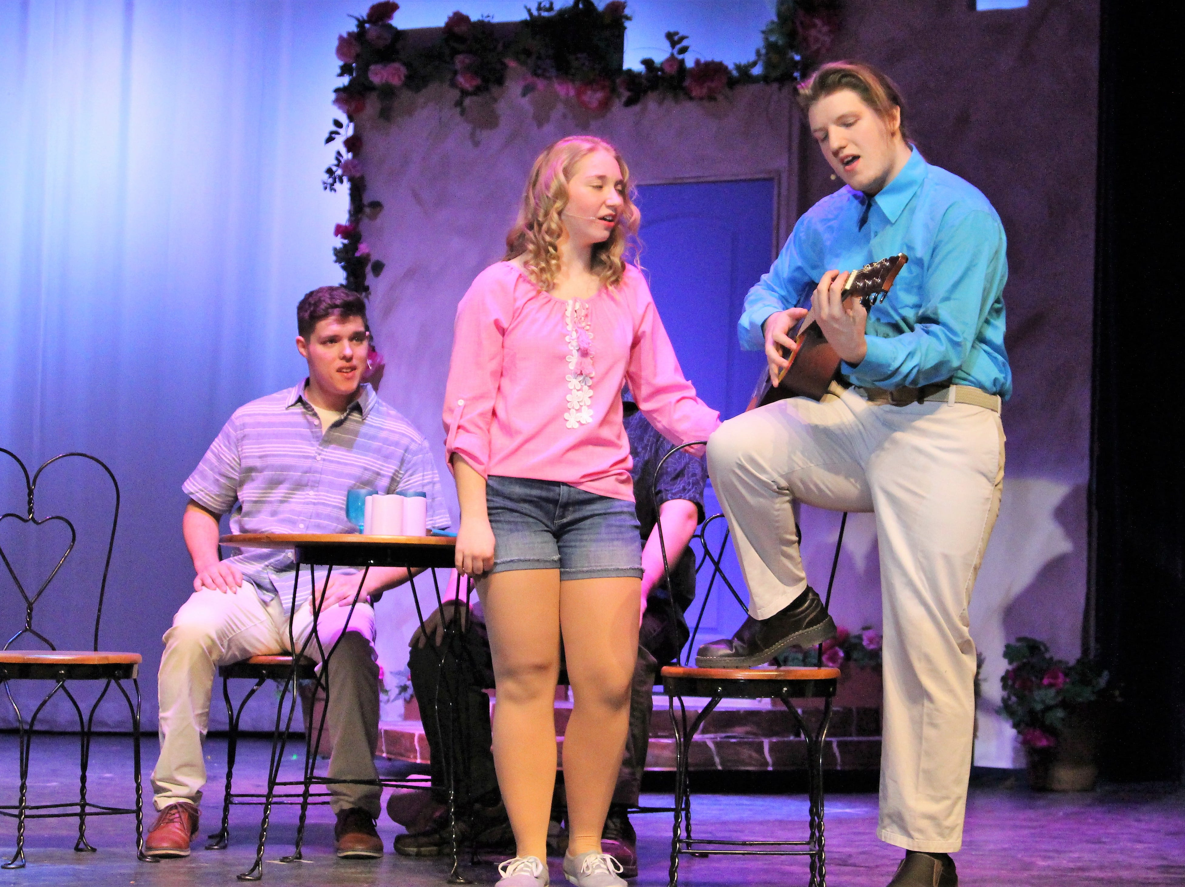 "River Valley Junior Annie Emigh —playing Sophie Sheridan, a young bride searching for her father— joins senior Ryan Anderson —playing British banker Harry Bright— in song during a Tuesday evening dress rehearsal for the jukebox musical ""Mamma Mia."""