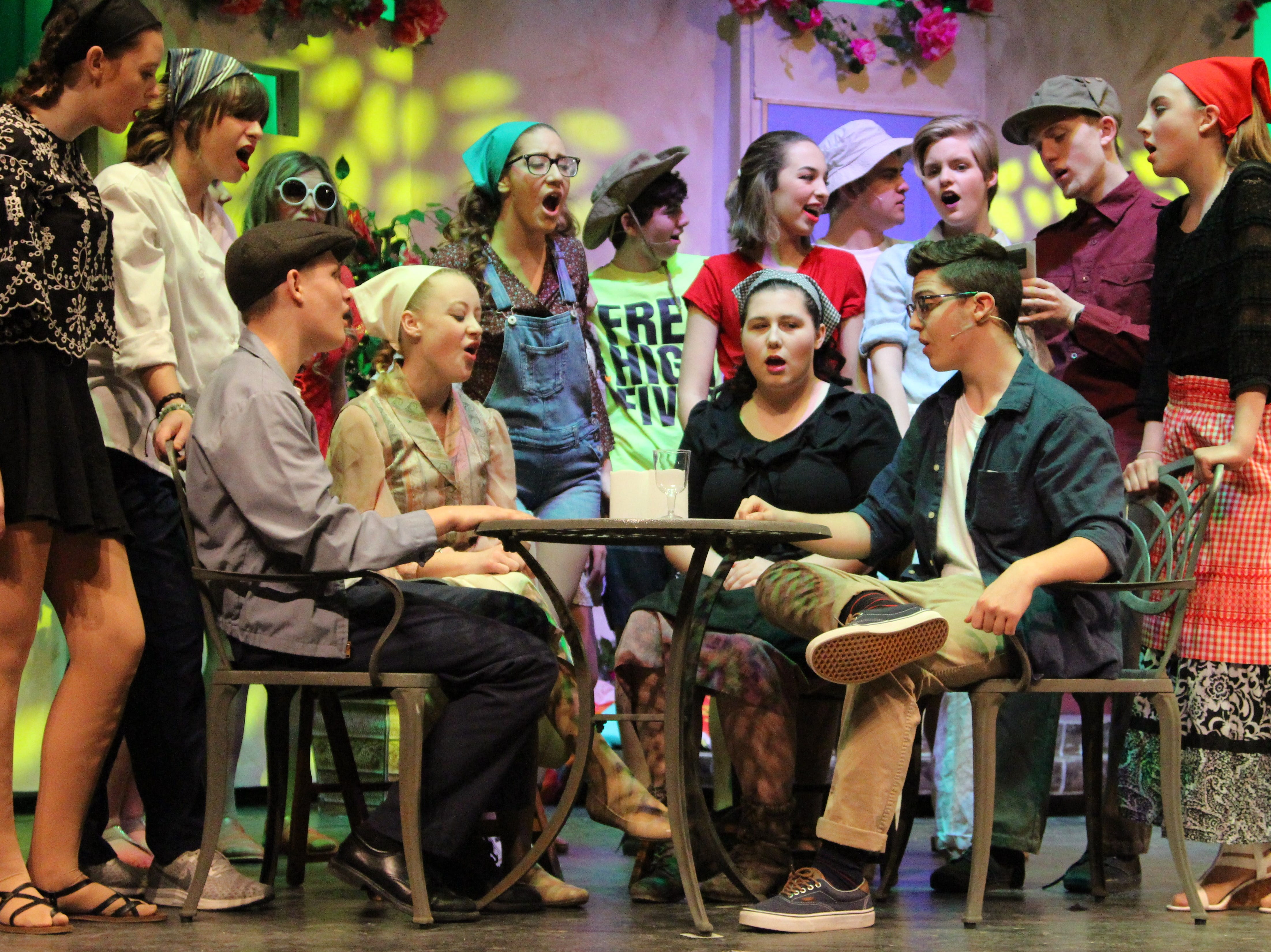 "Students gather around a ""taverna"" on the fictional Greek island of Kalokairi during a Tuesday evening dress rehearsal of River Valley High School's production of ""Mamma Mia."" The show will be open to the public this weekend."