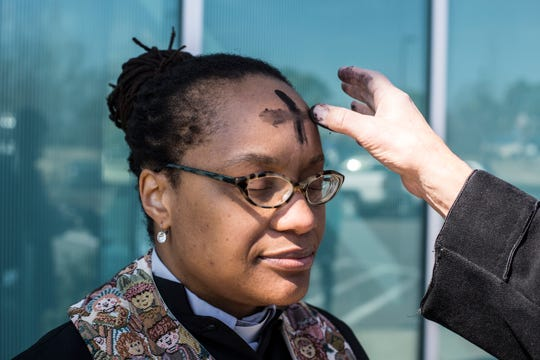 The Rev. Ayanna Watkins, lead organizer of MICAH, receives ashes before offering to place ashes on the heads of migrants traveling through Memphis on Ash Wednesday at the Greyhound bus station.
