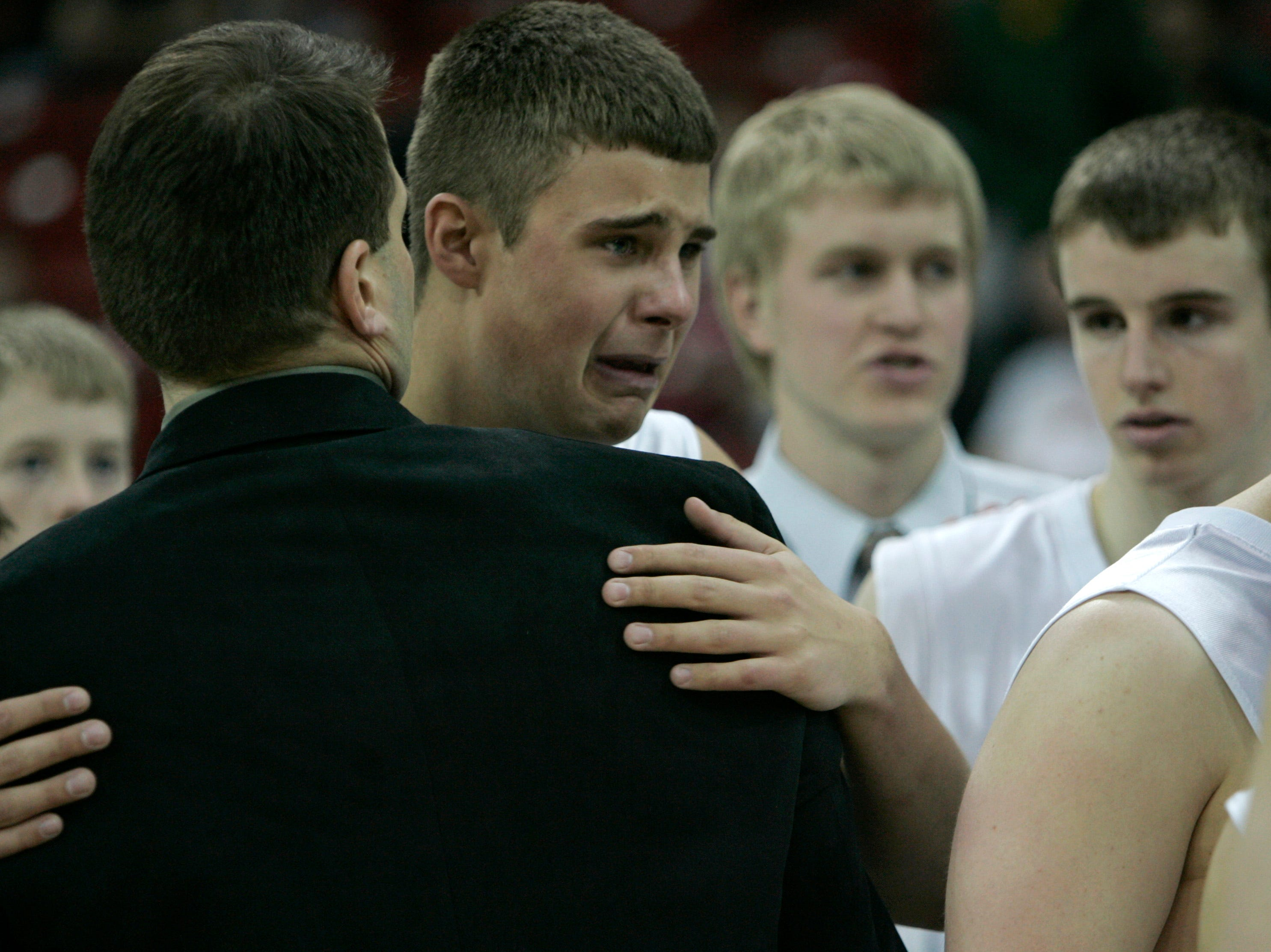 Port Washington Pirates' Jon DeBoer hugs head coach John Bunyan  after losing 52-46 to the Monroe Cheesemakers' in the Boys WIAA State Basketball Tournament Divisioon 2 Finals, being held at the Kohl Center in Madison. March 17, 2007.