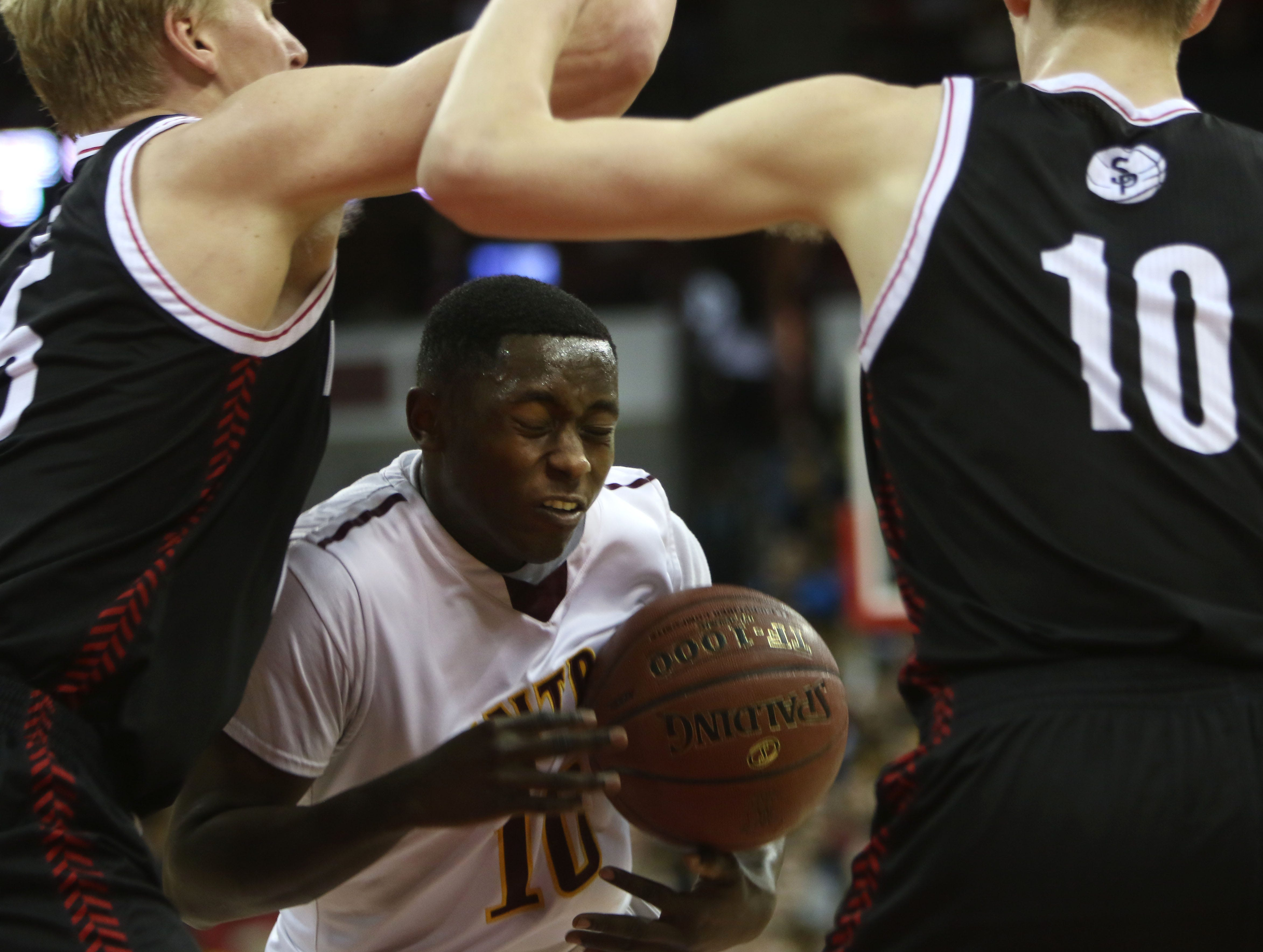 West Allis Central's  Jerome Cummings attempts to drive between Stevens Point's Andrew Ruzek (left) and Sam Hauser (10) during the second period of a 2015 WIAA Division 1 semifinal game.