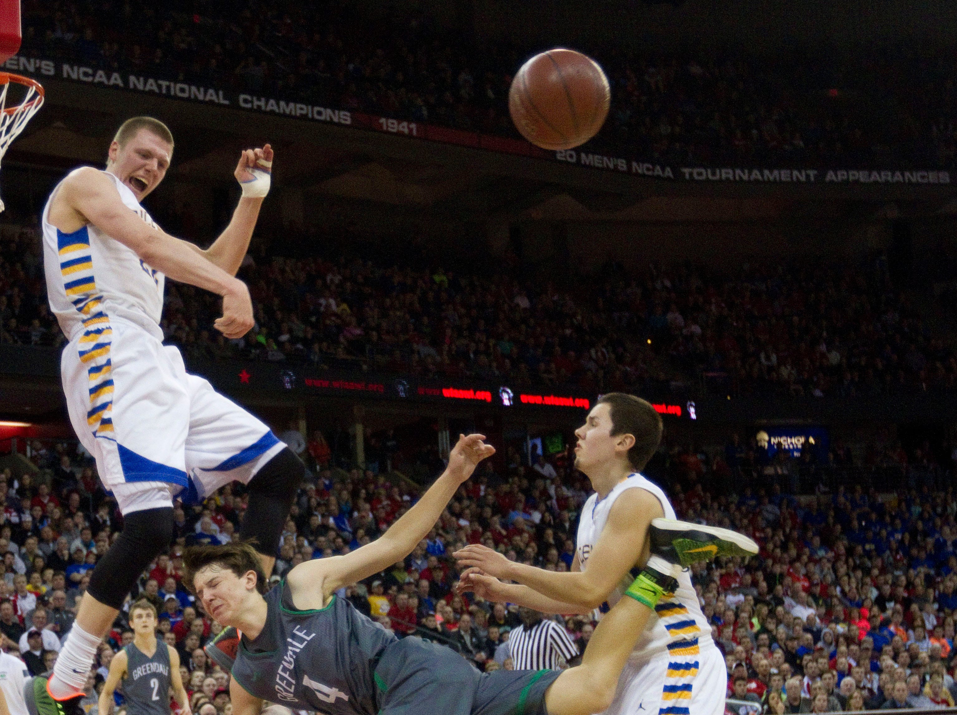 Greendale's Nate Thompson collides with Rice Lake's Henry Ellenson (left), Hunter Ashlin (24), and Erik Hovde (right) during the fourth period of the teams WIAA Division 2 Semi-Final Game  in the University of Wisconsin Kohl Center Friday, March 20, 2015, in Madison, Wisconsin.  Rice Lake won the game 72-64.