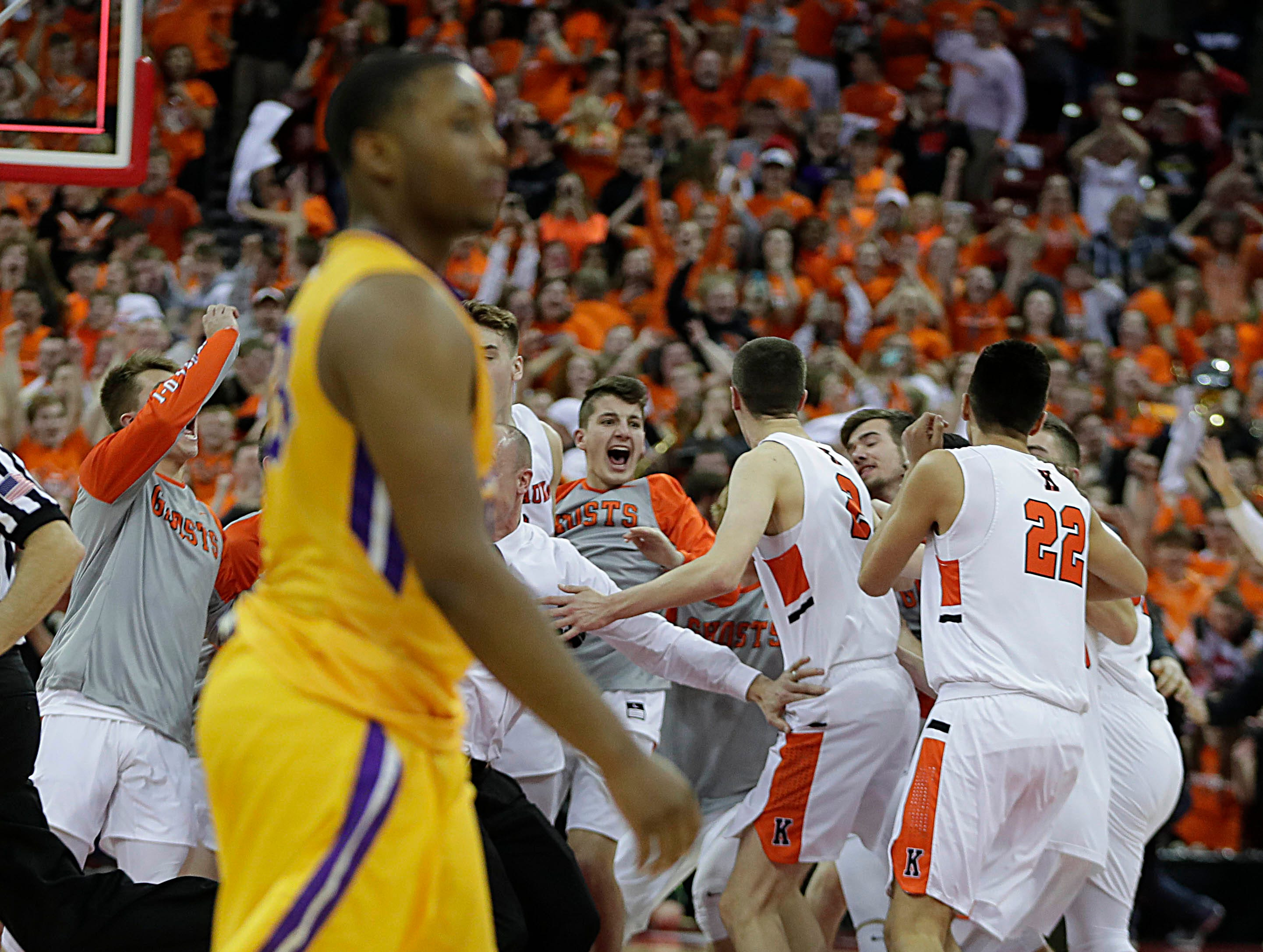 Washington players  show disappointment as Kaukauna reacts after  Kaukauna's 76-74 win over Washington in the 2018 Division 2 Championship at the WIAA state boys state basketball tournament.