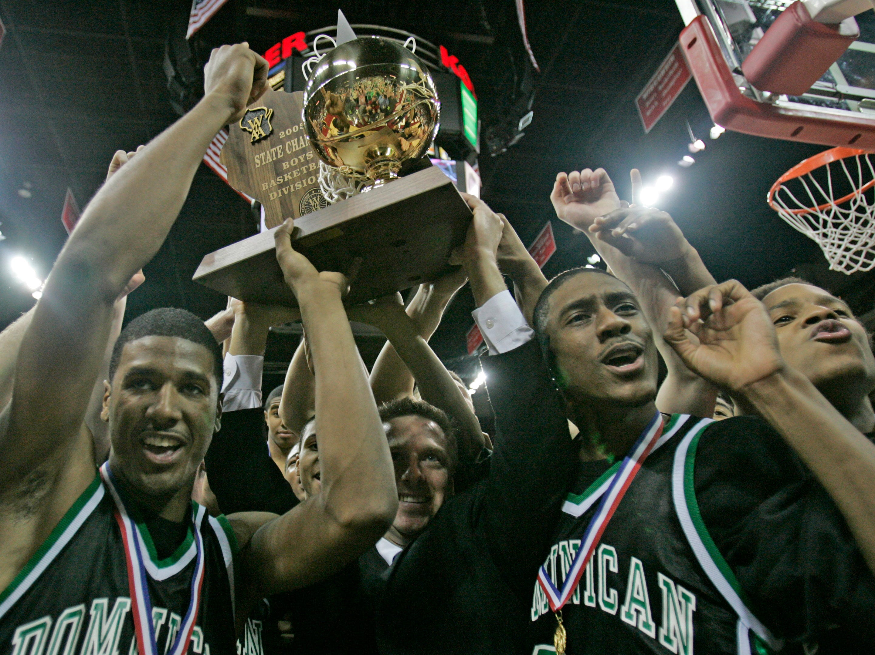 Whitefish Bay Dominican's Ben Hailey (left), coach Paul Wollersheim, Brandon Brown, along with Walter Blount Jr., hold up the 2005 Division 3 trophy after their 66-57 win over Grantsburg.