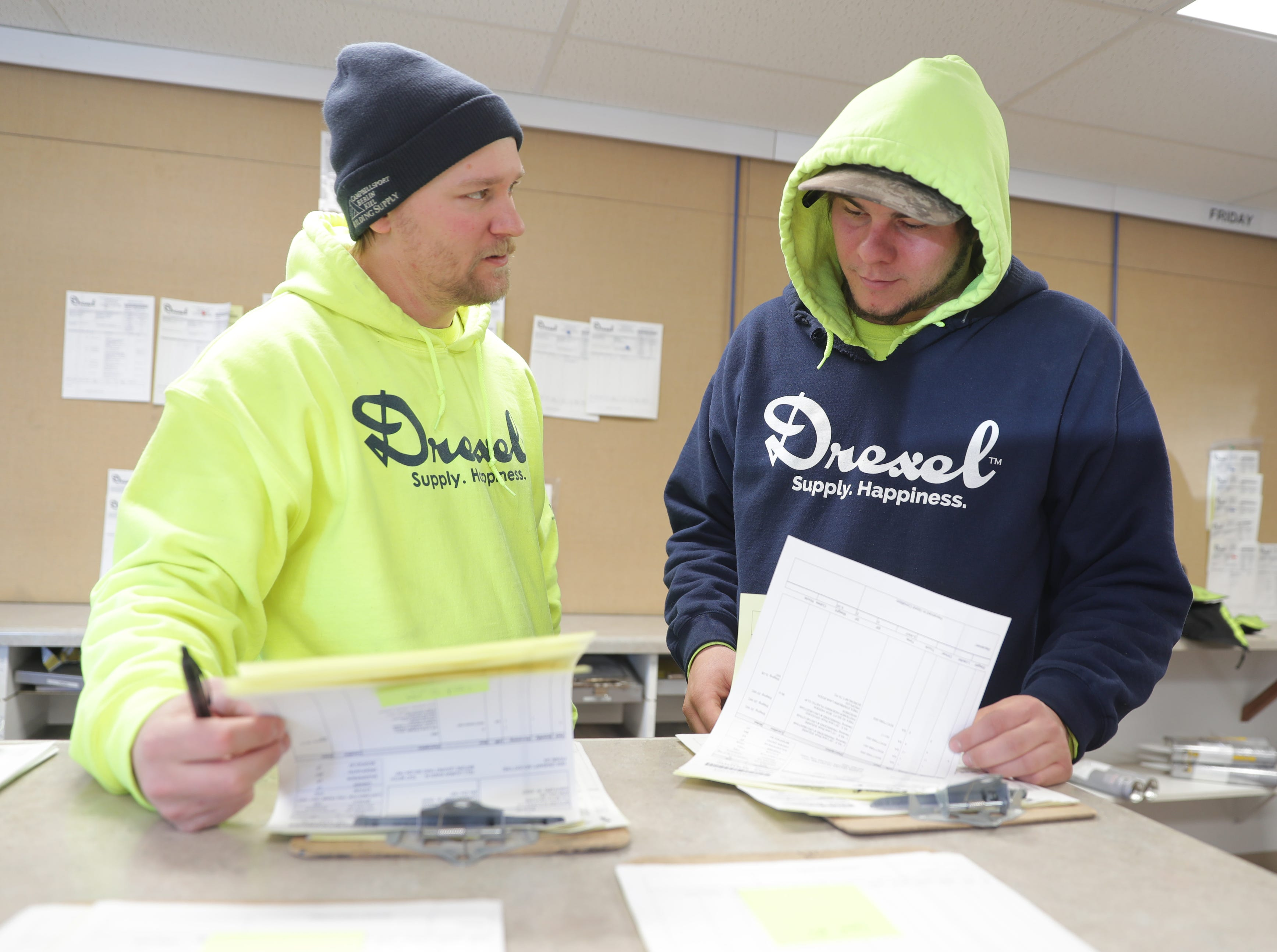 Drexel Building Supply Inc. Head Dispatcher Ryan Walsh (left) and operations dispatch employee Ty Schmidt organize orders to be loaded March 5 at Drexel Building Supply Inc.  in Campbellsport.
