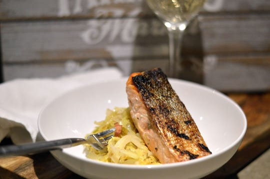 Sautéed savoy cabbage serves as the base for seared salmon fillet.