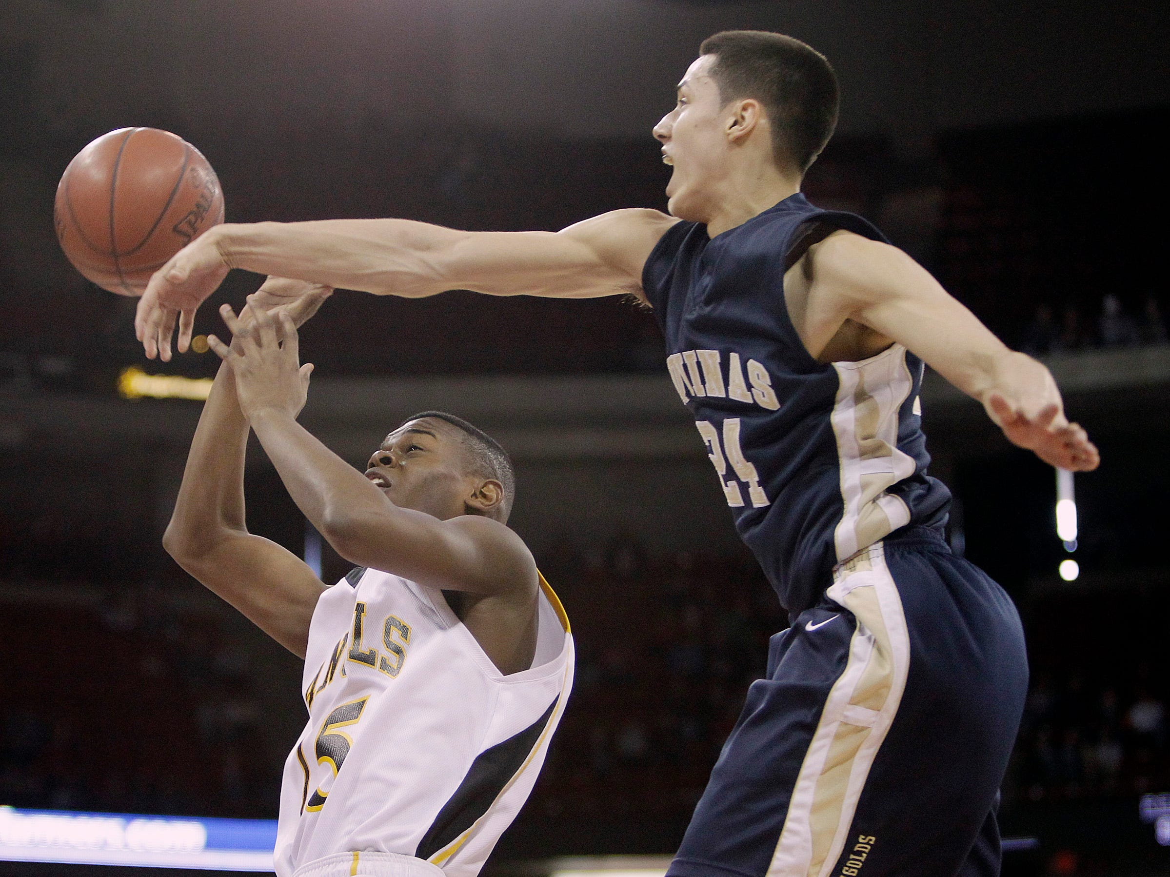 Aquinas's Bronson Koenig rejects a shot by  Racine St. Catherine's  Chris Souter during the WIAA state basketball tournament at the Kohl Center Saturday, March 19, 2011.