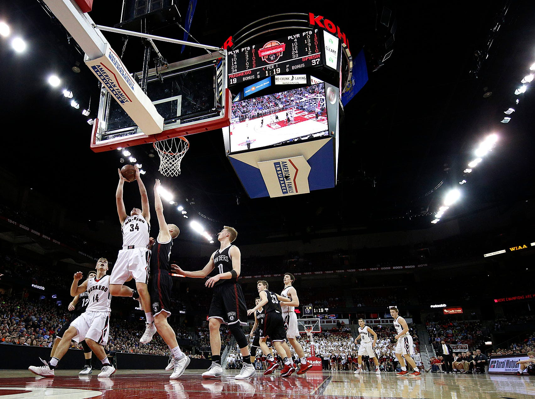 Muskego's  Tommy Andeson (34) attempts to shoot over Stevens Point's Sam Hauser as Matty Faner (14) looks on  during  the teams W.I.A.A. Boys State Basketball Tournament championship game in the Kohl Center Saturday, March 19, 2016, in Madison, Wisconsin. Stevens Point won the game 89-64.