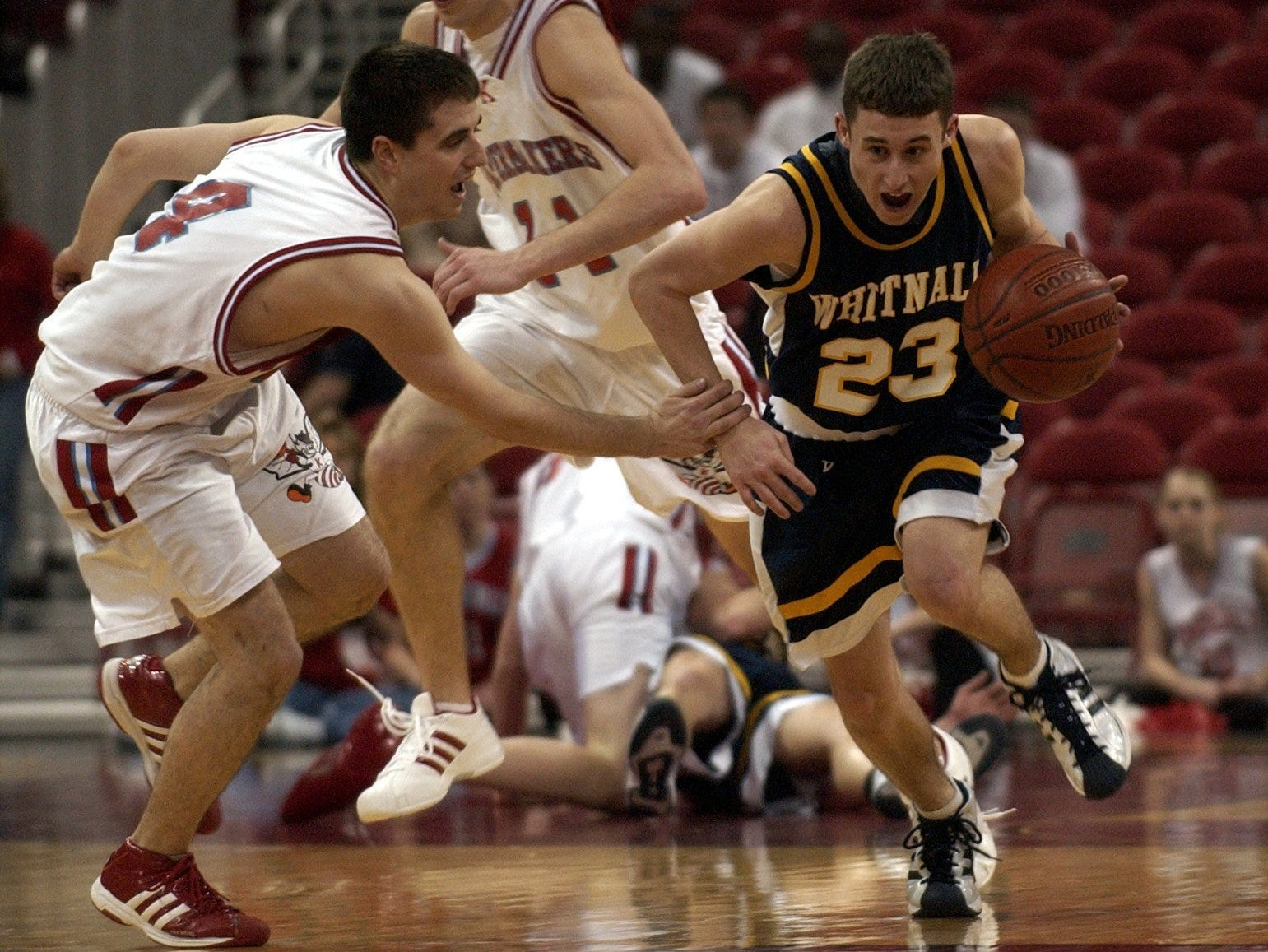 Whitnall's Nick Romans, (23) despite Kimberly's Mark Reider (4) efforts, makes the most of a loose ball, converting the play for a layup at the other end of the court. Kimberly prevailed 37-33 over Whitnall to advance in the WIAA Division 1 basketball quarterfinal game at the Kohl Center in Madison, Thursday, March 18th, 2004.
