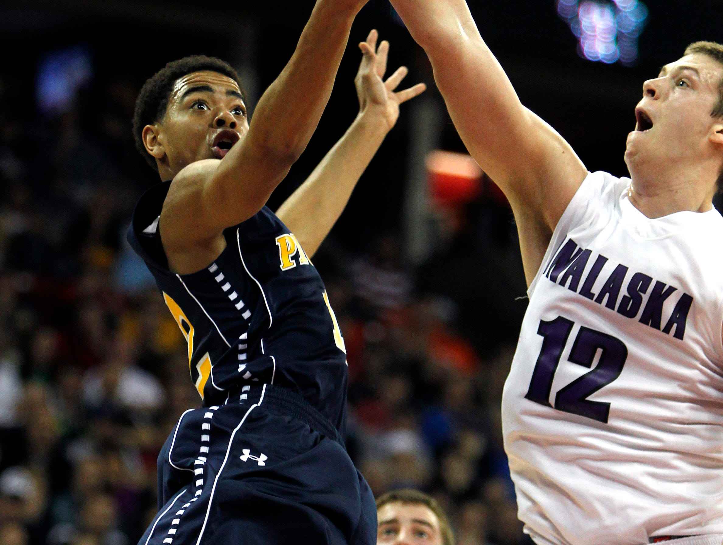 Milwaukee Pius XI's Carrington Love lays the ball up under the arm of Onalaska's Nick Arnez during the second quarter of the game at the WIAA boys state basketball tournament held at the Kohl Center in Madison, WI Friday March 16, 2012.