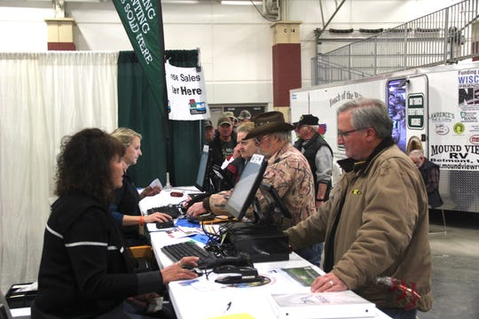 Customers, including Mike Derdzinksi of Elm Grove (right), buy licenses on Wednesday, March 6 at the Department of Natural Resources exhibit at the Milwaukee Journal Sentinel Sports Show in West Allis.