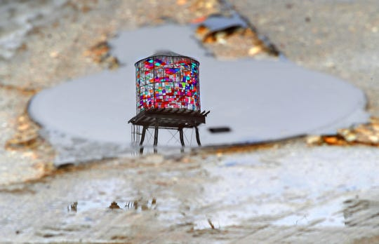 The Coakley Brothers Co. building mosaic water towers is reflected in a puddle on South 5th Street in Milwaukee on Wednesday, Feb. 27, 2019.