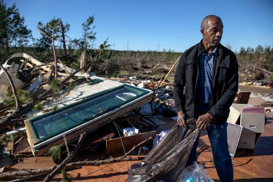 """Richard Tate retrieves personal items from what's left of his home where he survived a tornado with his wife in Beauregard, Ala., Tuesday, March 5, 2019. Tate lost a sister, brother-in-law, nephew, and uncle in the storm, all who lived nearby. """"I'm lucky to be alive,"""" said Tate. """"It could have taken all of us the way it was moving."""" (AP Photo/David Goldman)"""