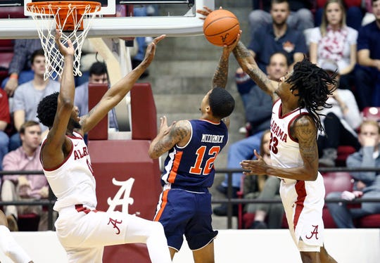 Alabama guard John Petty (23) knocks the shot of Auburn guard J'Von McCormick (12) during the second half at Coleman Coliseum on March 5, 2019.